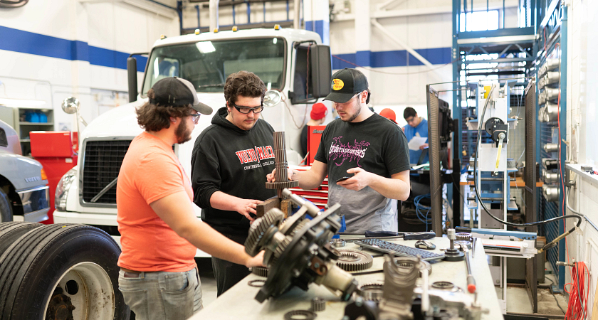 A group of three students in the Heavy Duty Motive Power program working in the classroom