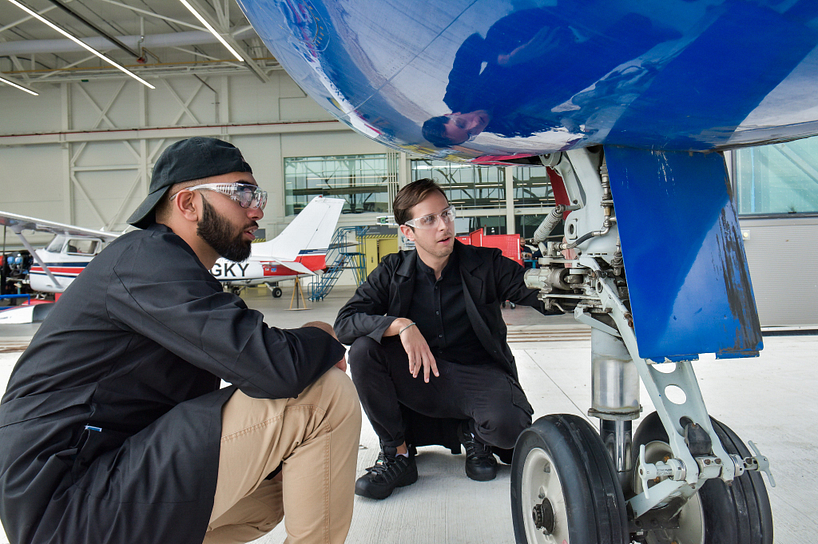 a centennial college student and faculty member inspecting an airplanes landing gear