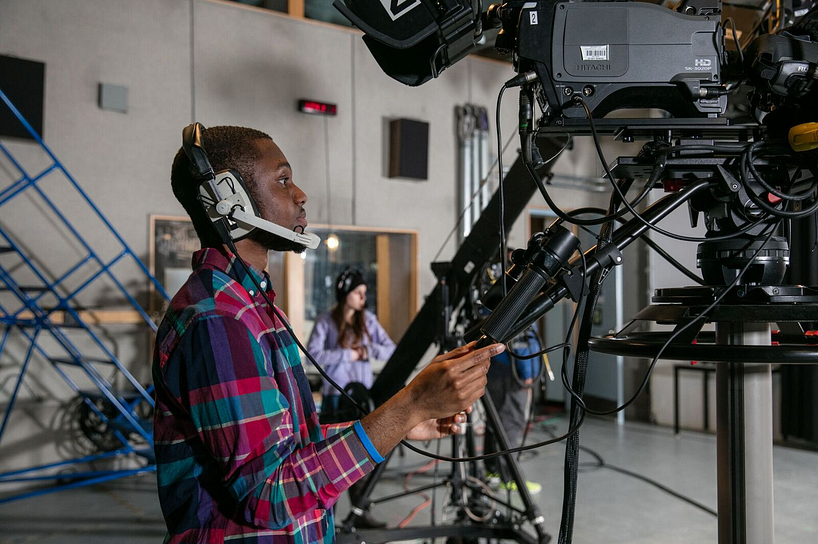 broadcasting student using a camera in a professional studio