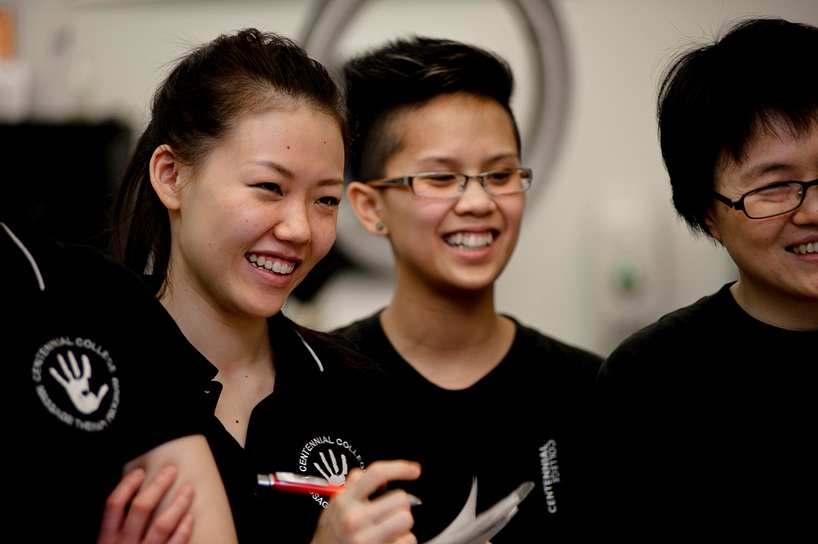 centennial college massage therapy students smiling while taking notes and listening to an instructor