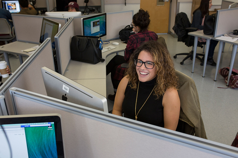 A journalism student smiling at her computer desk in class