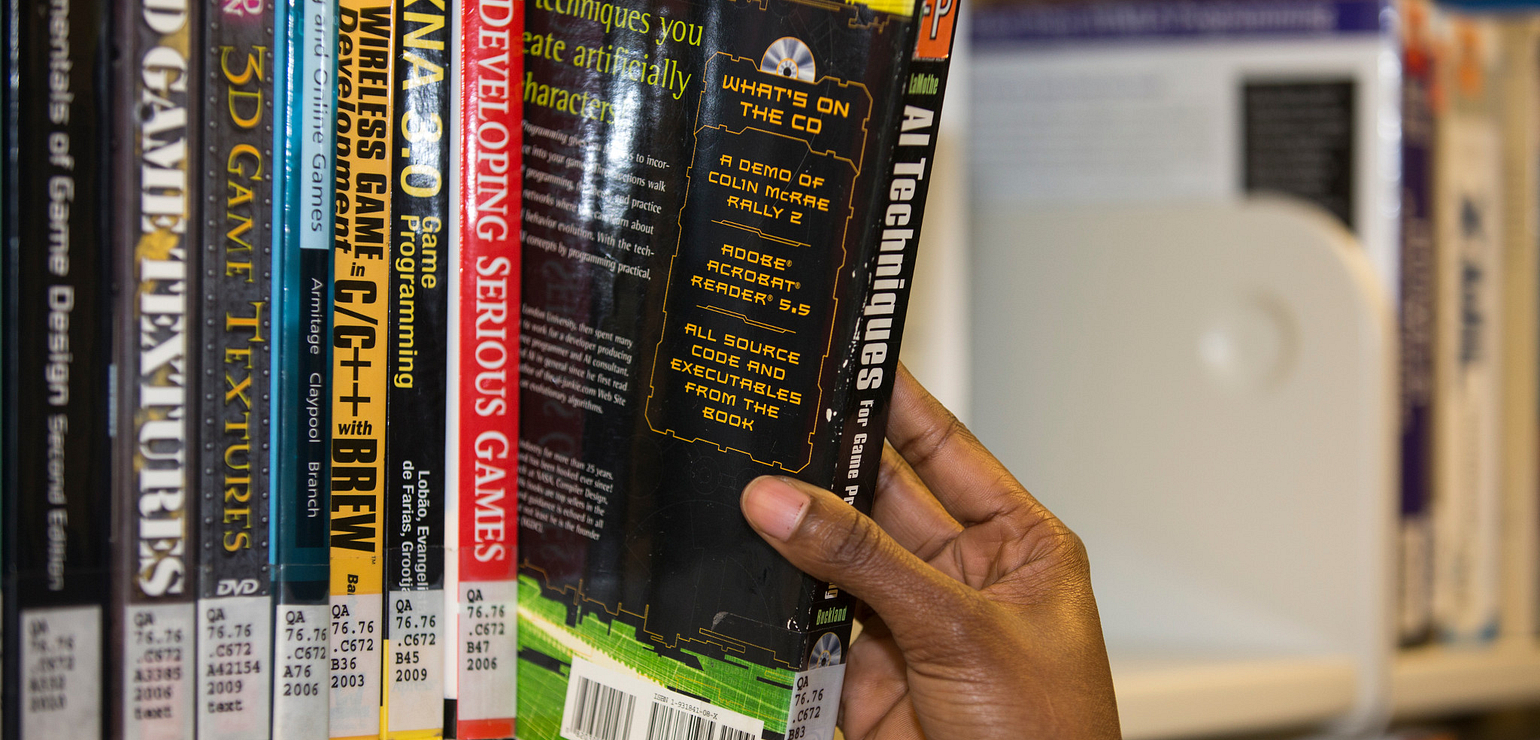 a hand pulling a book from the shelf in the library for the grab & go service