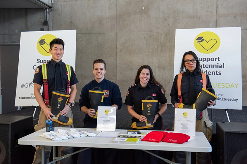 centennial college pre-service firefigther students smiling while taking donations for our giving tuesday event