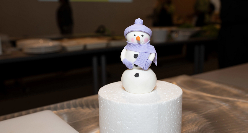A picture of a cake with a snowman made of icing on top