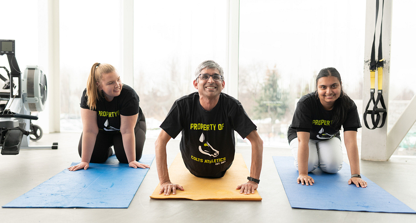 A group of three students doing yoga
