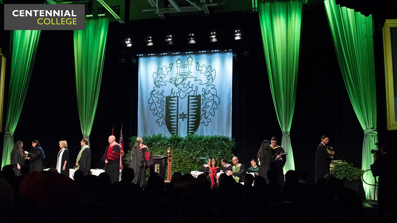 picture of the centennial college convocation stage with graduates walking across shaking hands with faculty