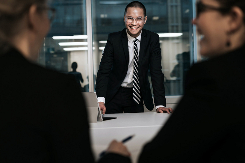 Male business student smiling in a meeting