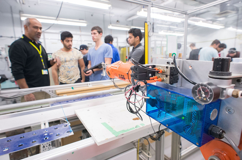 centennial college students and instructor showing a robotic arm