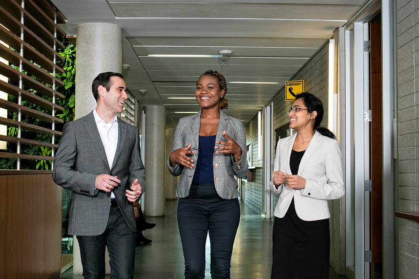 centennial college student walking through a hall smiling while talking to two colleagues