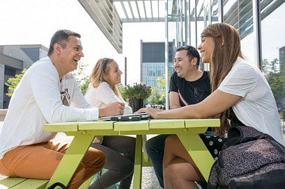 centennial college alumni talking and smiling at a picnic table