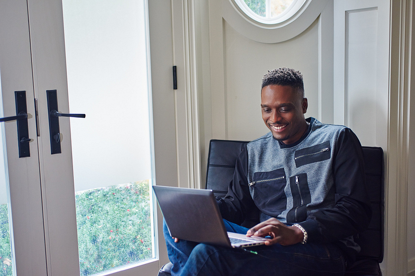 future student smiling while on their laptop attending an online open house webinar