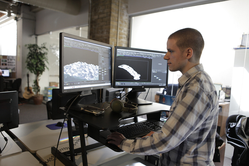 A digital visual effects student creating a complex landscape graphic on his desktop computer in class