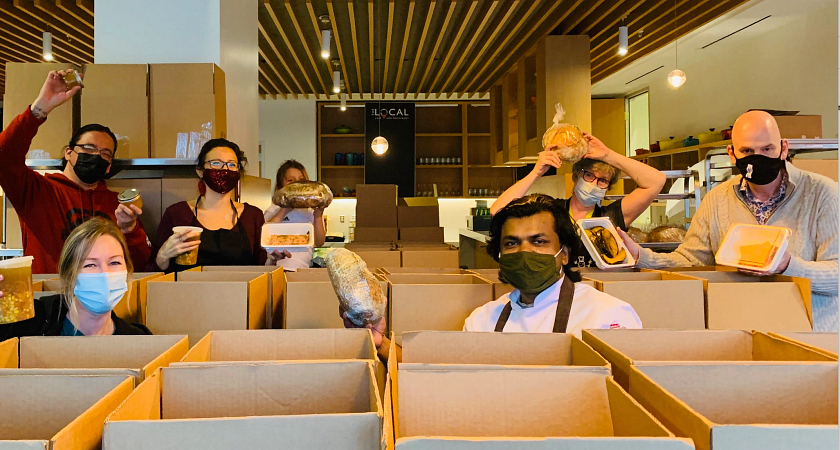 centennial college community members preparing food boxes for donation while wearing masks