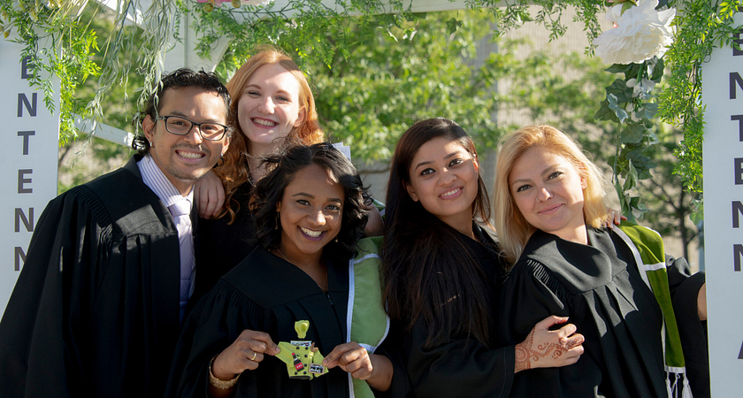 graduates smiling and posing together in the progress campus courtyard