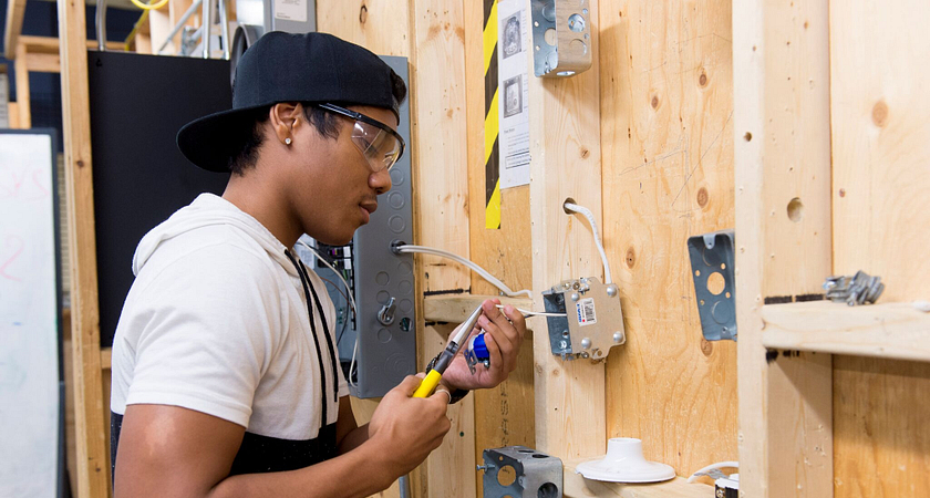 centennial college electrician pre-apprenticeship student working on a breaker box