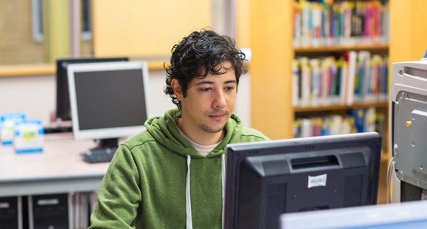 Male student sitting at a computer applying for OSAP