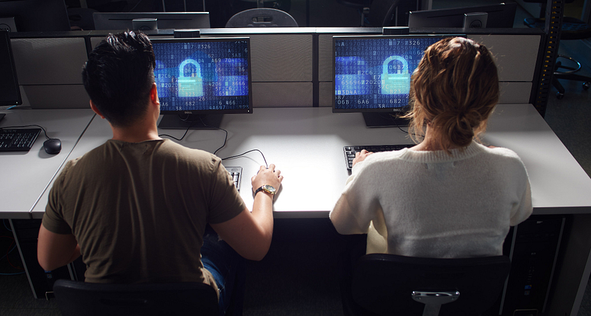 Two Cyber Security students sitting in front of two computers