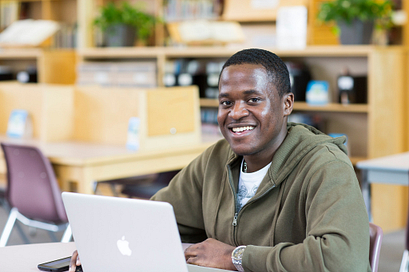 Male student smiling while working on his laptop