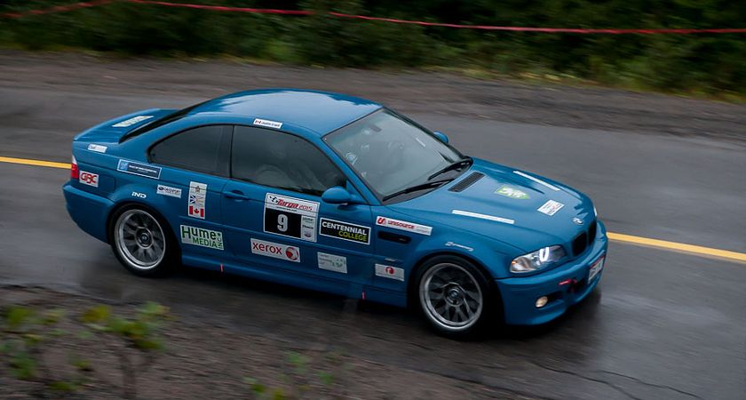 Picture of a blue BMW driving in the Targa Newfoundland competition with the centennial college logo on the side of the car