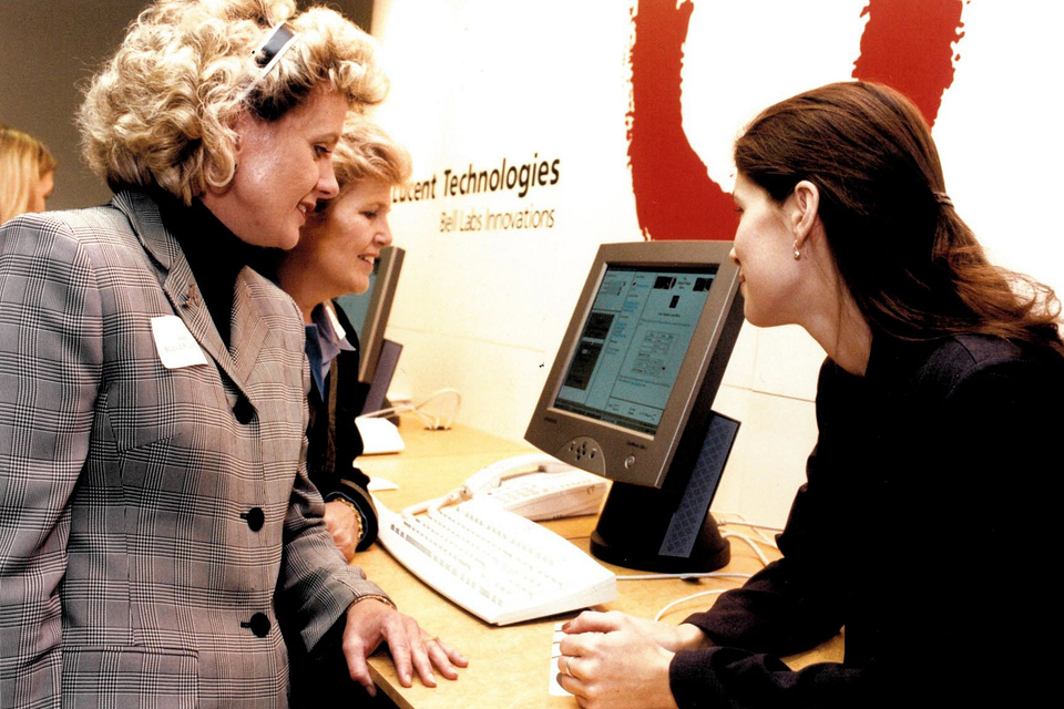 Photo of President Ann Buller visiting a Lucent Technologies display, 2000.