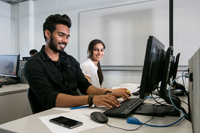 Two students working on their computer in class