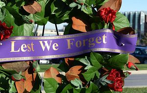 picture of a wreath with poppies and a ribbon that reads lest we forget