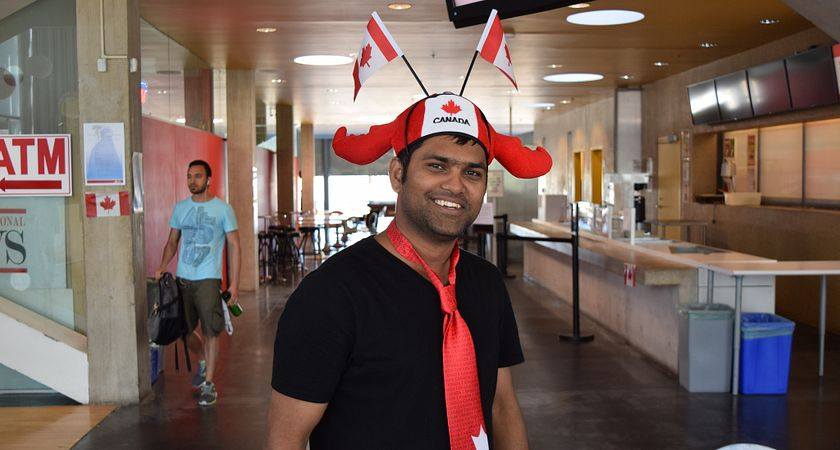Picture of a Centennial College student in the Student Centre wearing a Canada themed tie and hat.