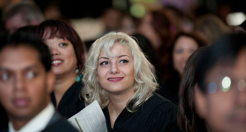 A female graduate looks ahead at the stage during the convocation ceremony
