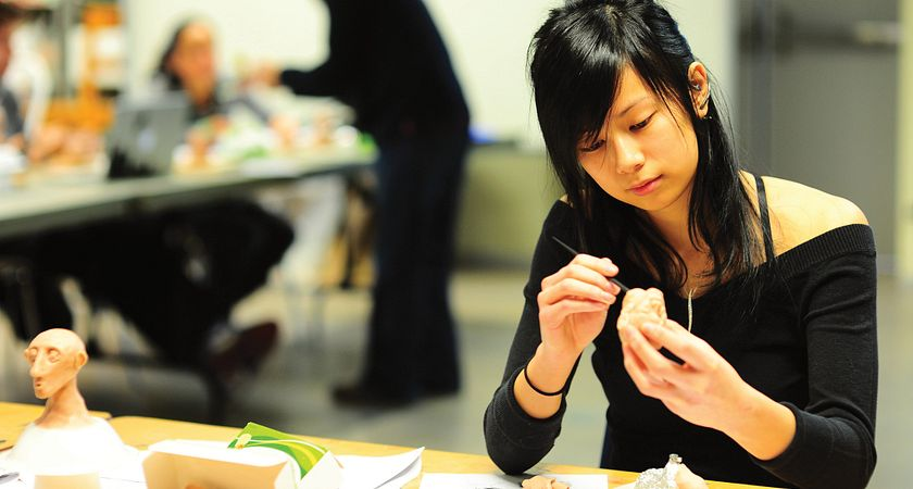 A female Fine Arts Studio student creates a model out of clay at the studio in the School of Communications, Media and Design