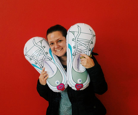 A Centennial College student poses with the Centennial Chase Mascot Shoesies