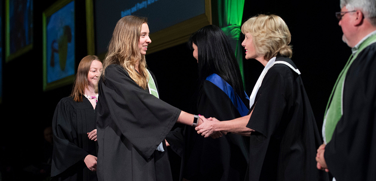 Picture of female graduating student at convocation shaking hands with the college president