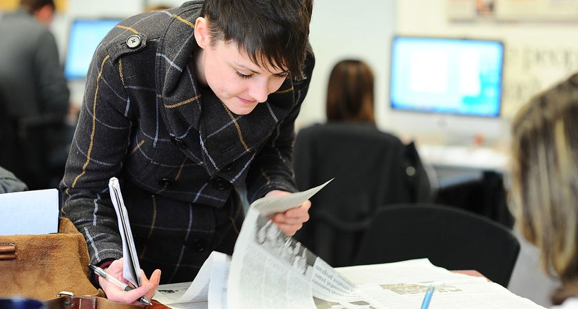 Female Journalism student crouches down to flip a newspaper, as she holds her pen and notebook, during a class at the School of Communications, Media and Design