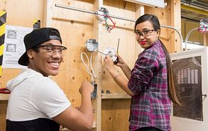 picture of two centennial college electrical engineering students working in a lab with safety equipment