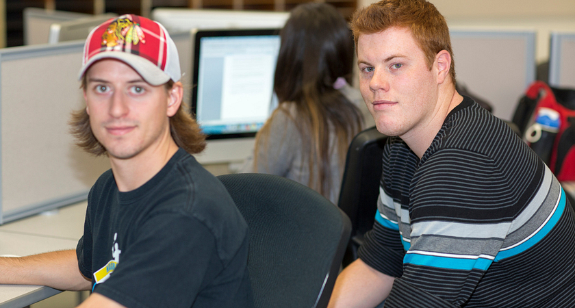 picture of two centennial college journalism students in the journalism lab