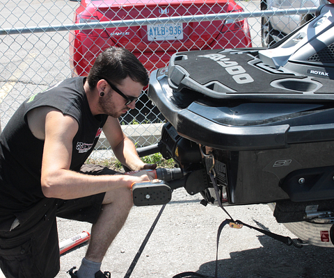Picture of Centennial College Motorcycle and Powersports Product Repair Techniques Alumni Jesse Chatten repairing a Seadoo