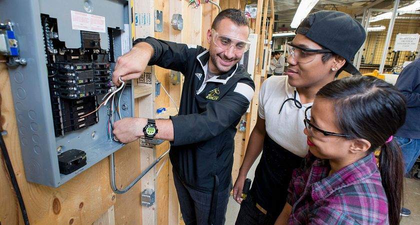 picture of centennial college electrical engineering students in a lab working with a  circuit breaker