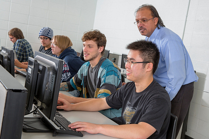 Students work in a computer lab with their professor overseeing their work