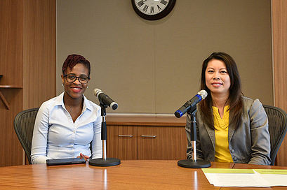 Two female speakers sitting behind a desk with microphones