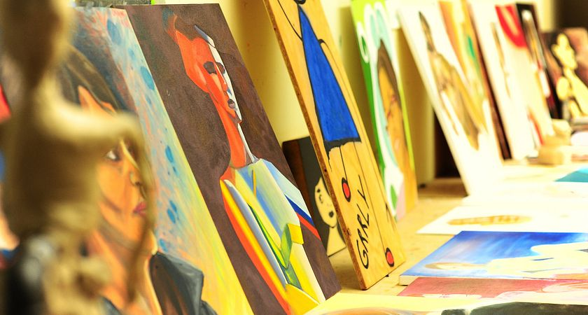 A row of works of art leaning by the wall and set on the table at the Fine Arts Studio at the School of Communications, Media and Design