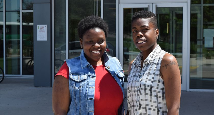 Picture of Centennial College Child and Youth Care graduates Denise Dunn and Priscella Millwood outside progress campus library.