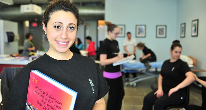 Picture of a health and wellness student with a textbook