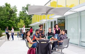picture of Centennial College students eating at a patio table at Progress Campus