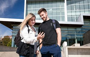 picture of centennial college students entering the national co-op week contest on their phone outside morningside campus