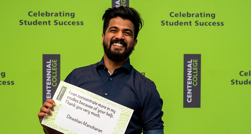 Picture of Dineshan Manoharan smiling while holding up a sign that says I can concentrate more in my studies because of your help, thank you very much
