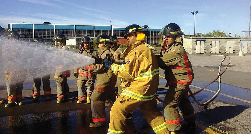 Group of eight male firefighters holding a firehose
