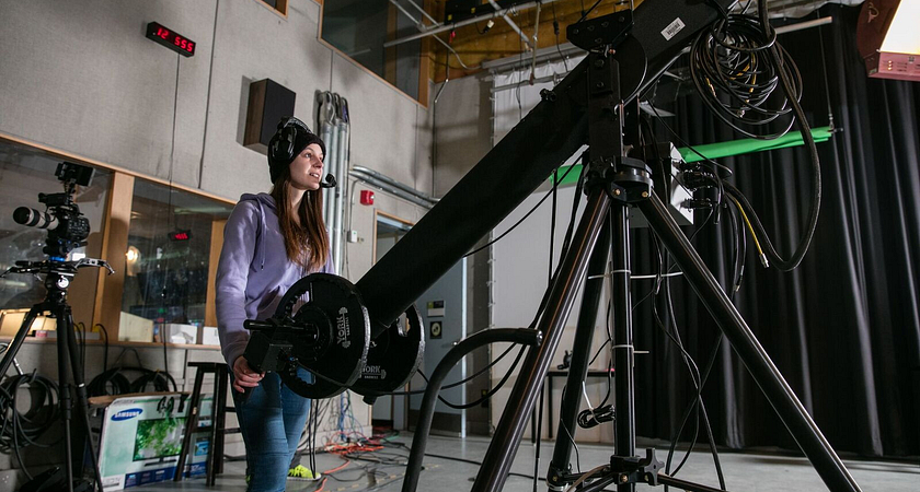 picture of a Centennial College Broadcasting - Radio, Television, Film & Digital Media program student in a professional studio filming with a camera on a camera crane jib