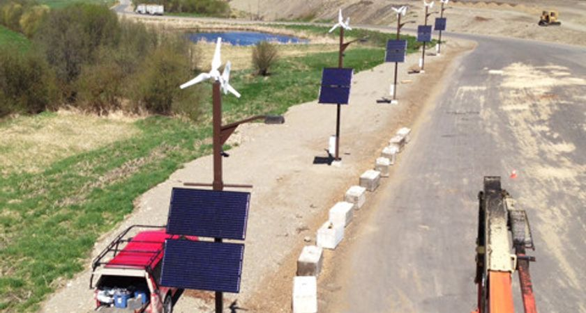 picture of windmills and solar panels by a road in the country