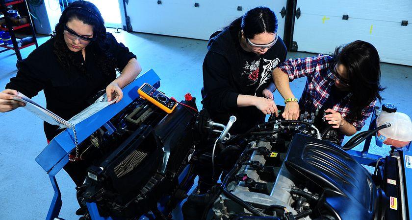 Centennial College Apprenticeship Program students working on an engine.