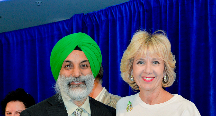 Picture of Centennial College School of Advancement team member Charan Batra Singh receiving an award from President Ann Buller