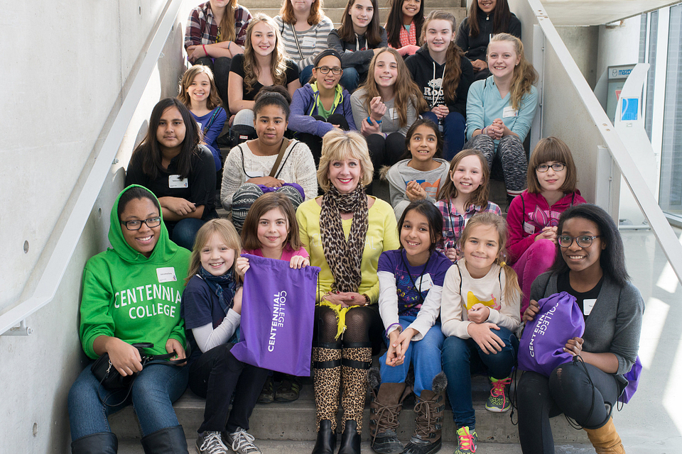 Photo of Ann Buller with a group of young girls visiting from Toronto middle schools for Strong Girls Strong Women, 2015.